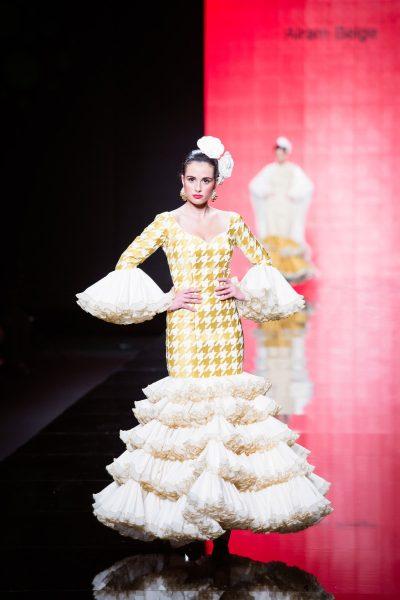 Vestido de flamenca de la colección Lady abril.Realizado en piqué beige. Cuerpo y mangas bordadas en pata de gallo amarillo dorado. Cinco volantes con adorno plisado de organza. Enagua canastera de batista beige.