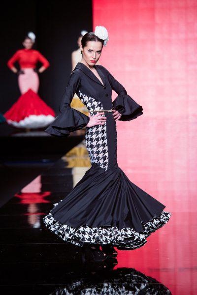 Vestido de flamenca de la colección Lady abril.De popelín negro con costadillos de organza bordados en pata de gallo negra. Cuello esmoquin. Enagua negra con volante beige bordado en pata de gallo.