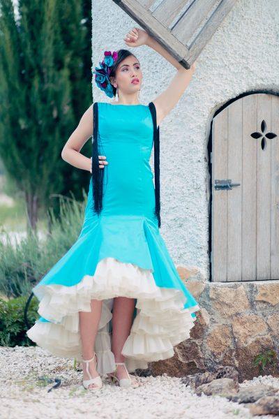 Vestido de flamenca en color azul turquesa con el bajo asimétrico ya enaguas en tono beige. Detalles de flecos negros en la espalda y caída en la parte de los hombros.