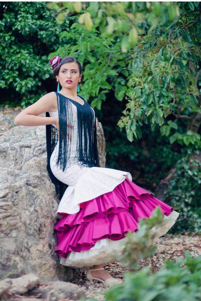 Vestido de tirantes en satén de algodón buganvilla y enrejado blanco. La falda lleva tres volantes, uno de enrejado y dos en color buganvilla con enagua beige. Flecos negros en los escotes.
