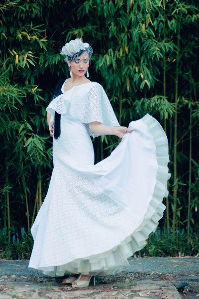 Vestido en satén de algodón con cuerpo y falda combinada con enrejado blanco. Enaguas en beige con dos volantes en buganvilla y azul. El traje es de manga asimétrica con volante en enrejado y detalles de flecos negros.