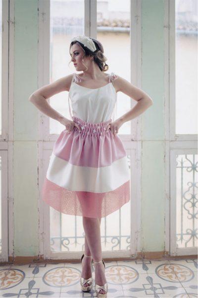 Falda fruncida en crepe rosa, crepe satén beige y organdí rosa empolvado bordado en hilo metalizado oro. Cinturilla ancha fruncida decorada con flores blancas cosidas a mano.