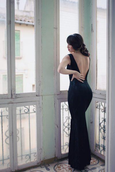 Vestido confeccionado en tejido de punto lurex negro. Escotes tanto delantero como espalda en forma de pico.Sin manga. Entallado. Con aperturas desde la rodilla a cada lado.